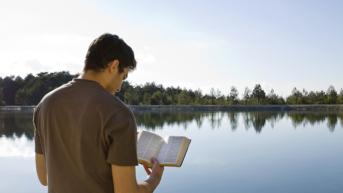 man reading bible near lake